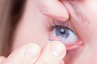 Woman holds a Contact Lens