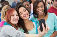 "Teenage girls taking ""selfie"" photo in busy classroom"