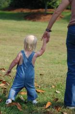 little girl holding her mother's hand