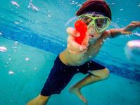 boy shooting water gun underwater