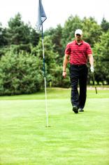 Golfer Walking Towards the Hole