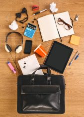 The contents of business briefcase on a wooden desk.