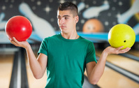 Confused young man holding bowling balls.