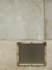 rusty metal ventilation grid embedded in concrete wall