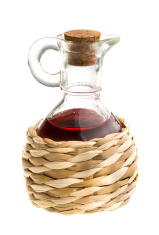 Small decanter with red wine vinegar isolated on the white