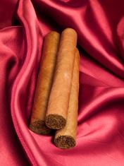 Three Cigars on red satin