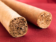 Two Cigars on red satin