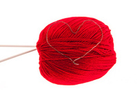 Knitting yarn with needles and a heart