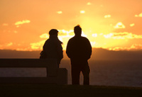 Sunset silhouette of man on bench