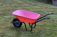 Empty pink wheelbarrow on mown grass