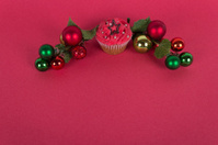 Christmas cupcake and tree ornaments on red background
