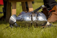 Helmet of the medieval knight on green field.