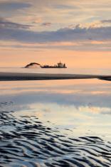 dredger pumping sand onto the coastline