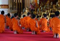 Buddhist monks praying in Thai temple.