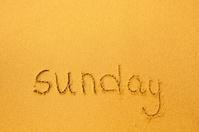Sunday - written in sand on beach texture.