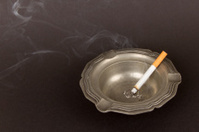 Burning cigarette in an old tin ashtray