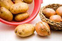 Fresh potatoes in the sieve and onion