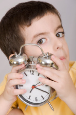 Boy listening the alarm clock