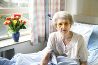 Senior Woman Sitting in Hospital Bed by Window