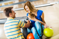 Beautiful young couple sitting at bowling alley.