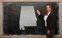 Teacher showing map of alabama on blackboard