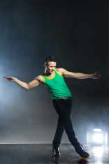 Dancer posing on background with flashes and smoke