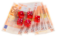Red dice on top of some 50 euro banknotes