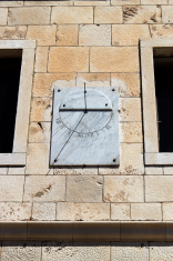 marble sun-dial between two windows