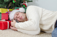 Drunk man with bottle sleeps under christmas tree
