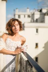 Beautiful woman enjoying morning sun on city balcony.