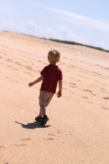 Toddler Boy Walking Alone on Beach