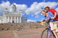 Couple having fun riding a bicycle in Senate Square, Helsinki