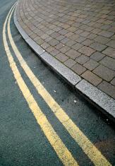 Asphalt curve with sidewalk and yellow line
