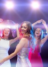 three smiling women dancing in the club