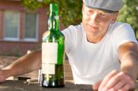 Melancholic drunk man looking at a bottle
