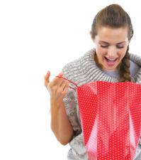 Closeup on happy woman looking in christmas shopping bag
