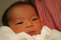 Newborn baby held by his mom