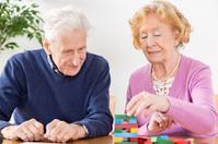 Nursing Home – senior couple playing with wooden blocks