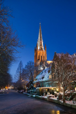 Illuminated church tower along frozen canal in winter - Holland