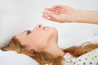 Sick woman using nasal spray.