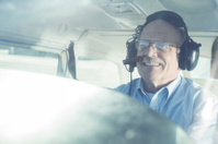 Smiling senior pilot in a small plane wearing radio headset