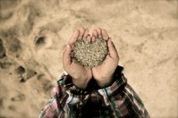 Heart shaped sand from beach in childs hands