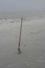 Shovel In the sand on a foggy day