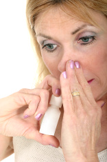 Woman Using Nasal Spray with Hand