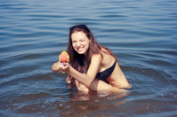 Happy young woman playing with water gun