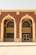 Architecture: High school building exterior. Arches, windows, do