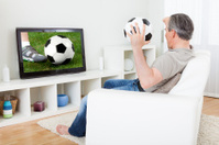 Mature man watching football on television