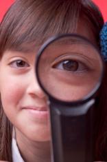 Girl looks through lens.