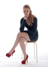 Pretty blonde girl in heels on a stool.