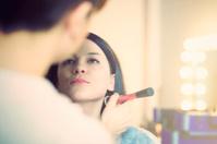 Make up artist preparing fashion model for photo shoot